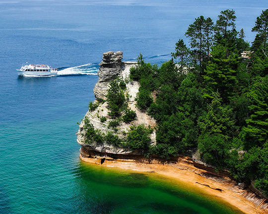 A tour boat on Lake Michigan moving past a spit of land covered in trees with a large, castle-like rock at the end of the spit.